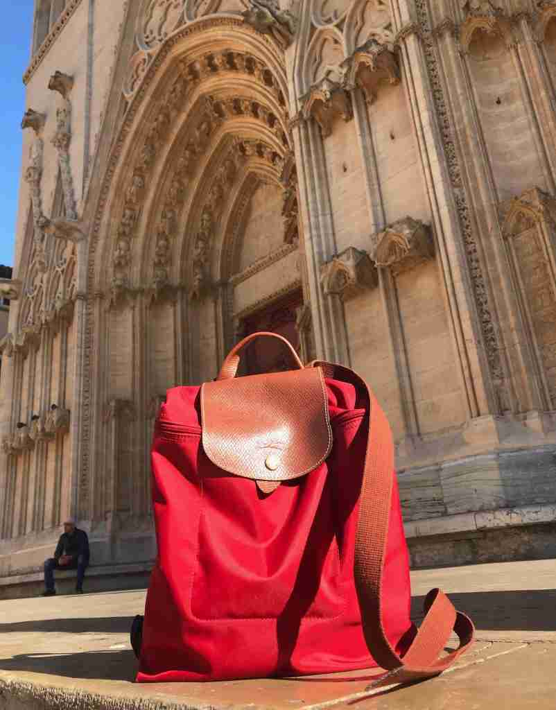 Red Longchamp backpack in front of a cathedral in Lyon, France