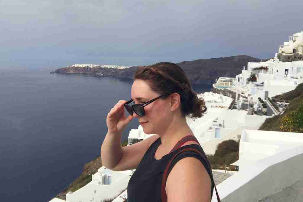 Solo female traveler against the white buildings of Santorini Greece