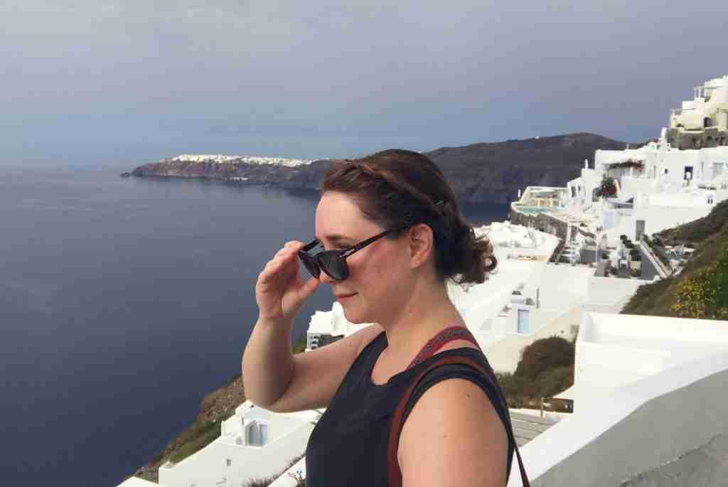 Solo female traveler against the white buildings of Santorini Greece