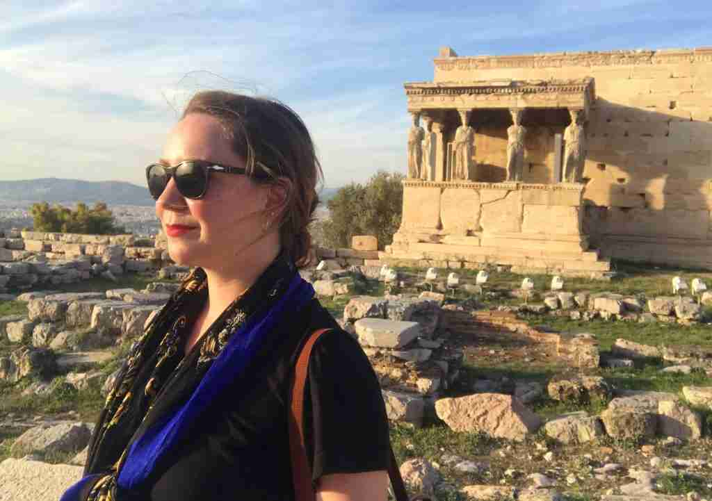 Solo female traveler at the Porch of the Caryatids at the Acropolis in Athens