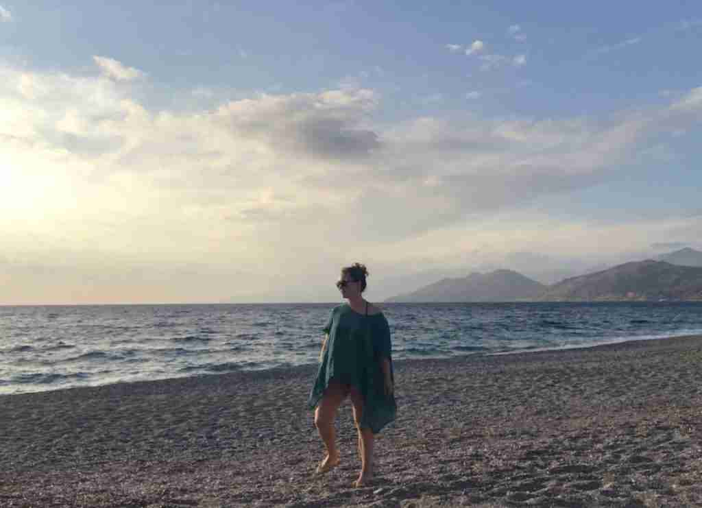 Solo female traveler on a beach in Crete Greece at sunset