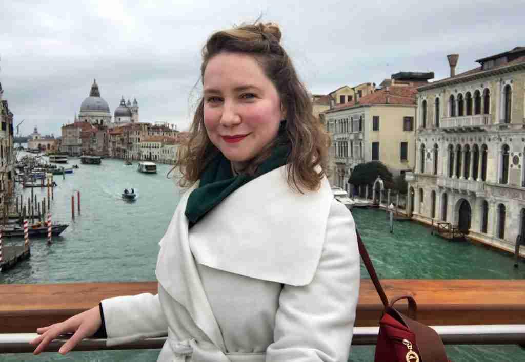 Solo female traveler on the Rialto Bridge in Venice, Italy