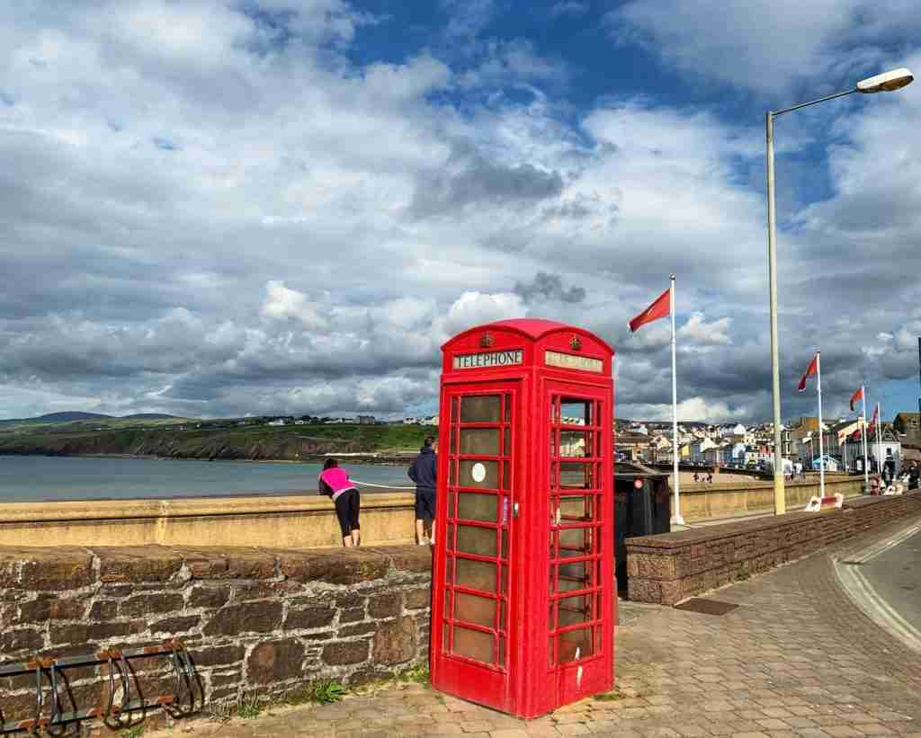 A red phone booth by the beach on the Isle of Man at Peel