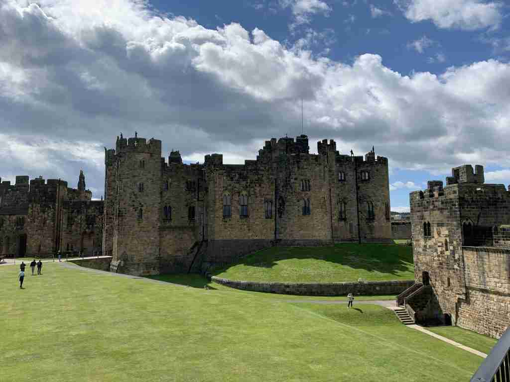 Alnwick Castle in Northumbria, England under a cloudy sky.