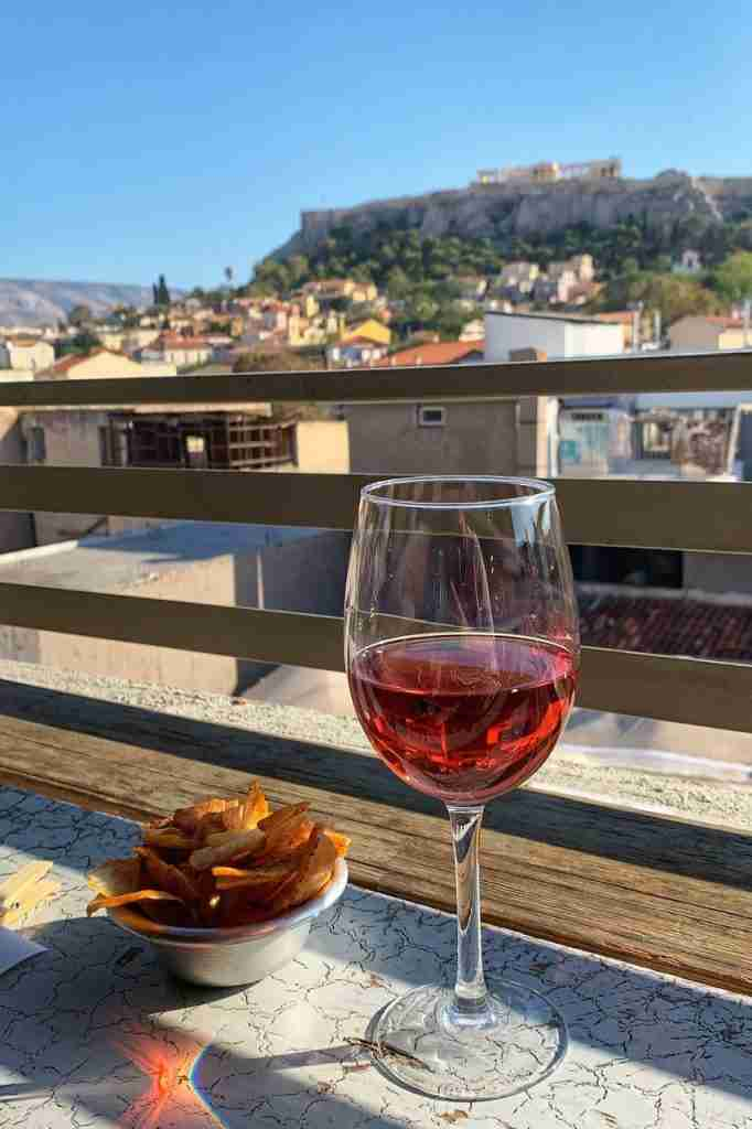 A glass of rose wine at a rooftop car Couleur Locale in Athens Greece