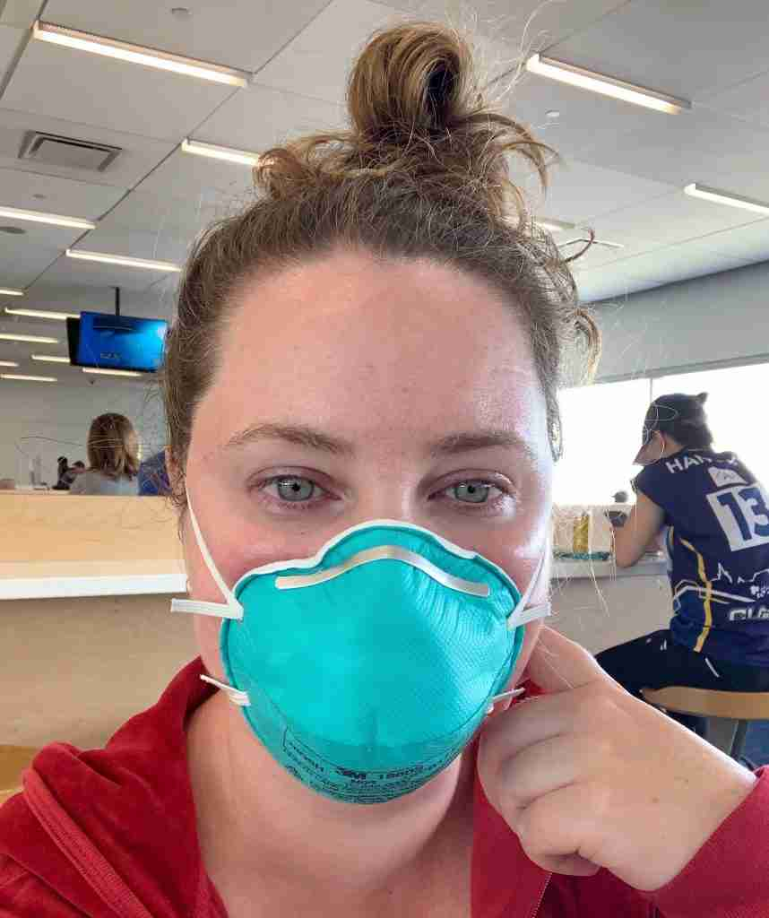 a solo female traveler wearing an N95 mask travel during pandemic