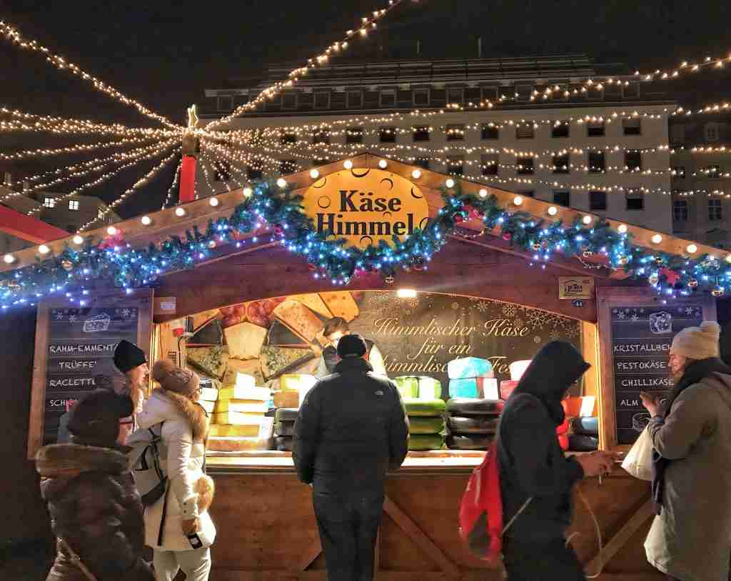 A cheese stand with lights at a Christmas market in Vienne, Austria