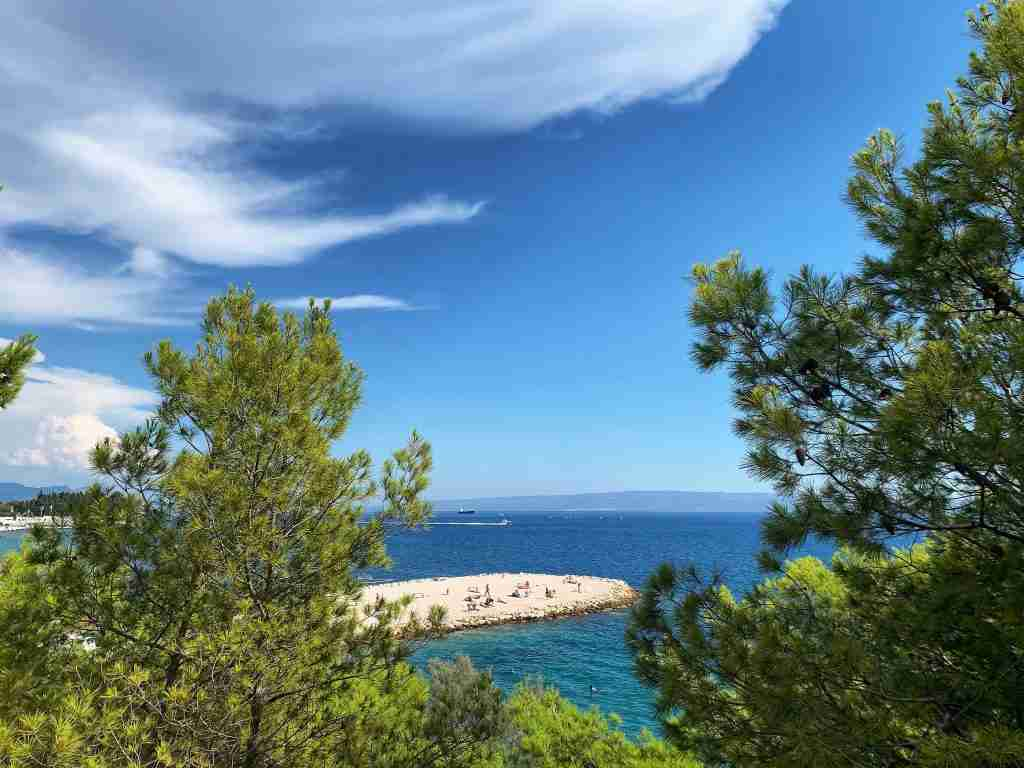 beach outside Split, Croatia with blue skies and green pine trees