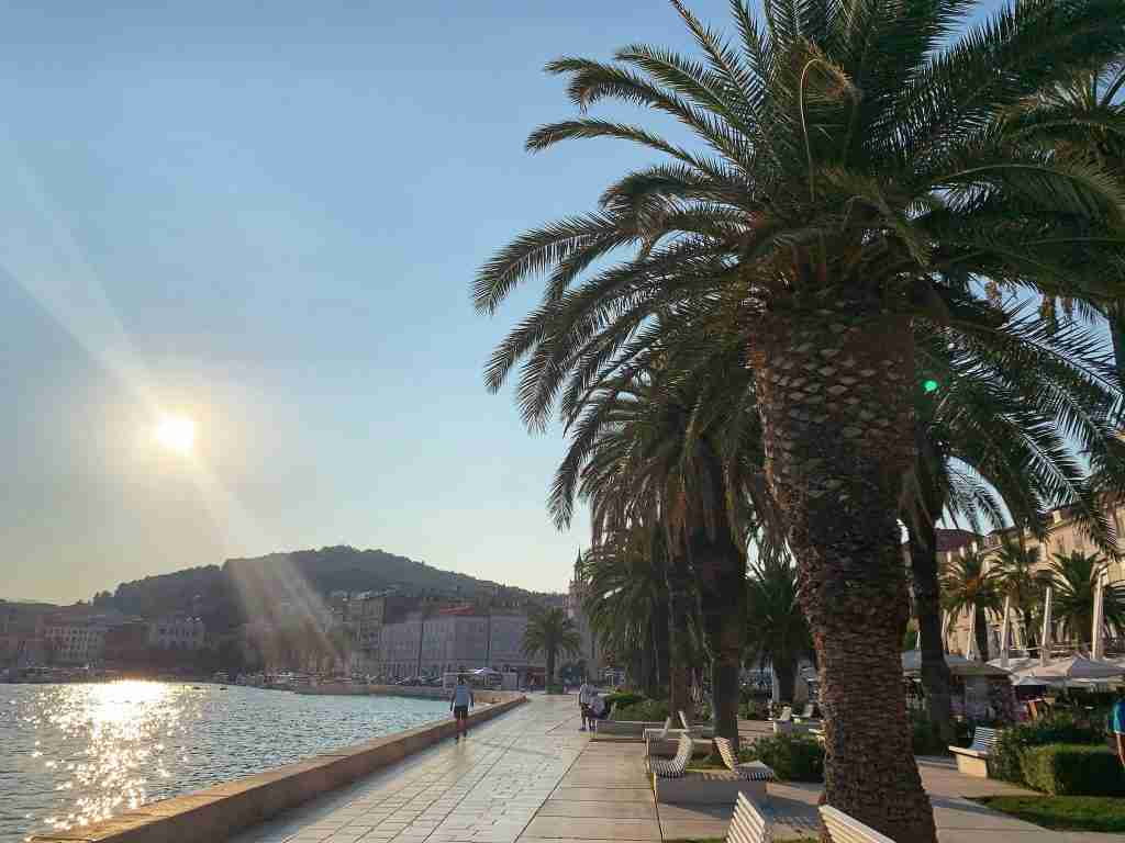 sun setting over the River in Split, Croatia with the sea and palm trees