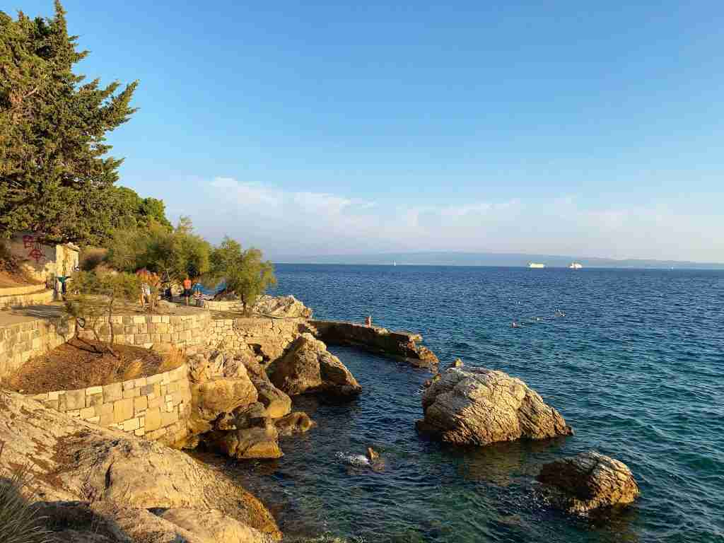 the rocky shore of a beach in Split, Croatia at sunset with swimming areas and cypress trees and the blue Adriatic Sea