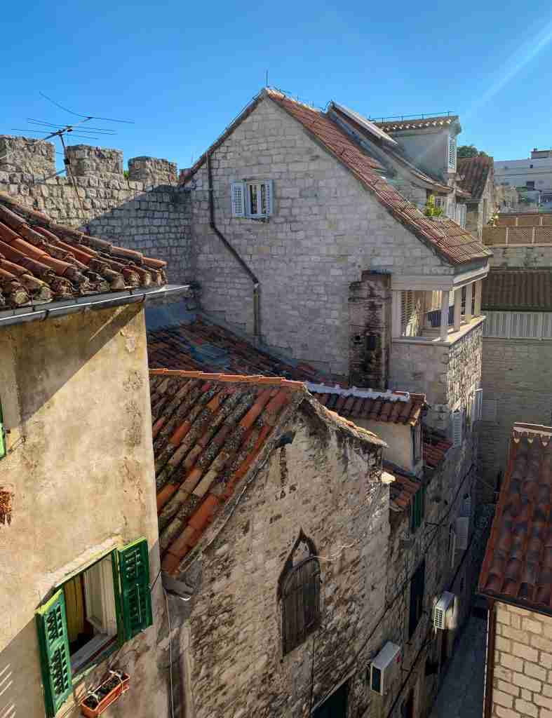 View from the Kaleta attic apartment in Split, Croatia against the ancient city walls on a clear, sunny day.